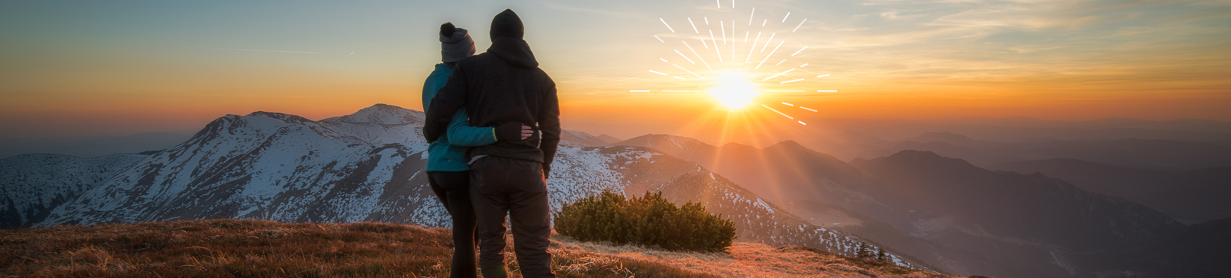 A couple standing at the top of a mountain watching the sunset